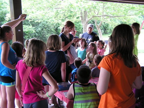 Emily bands a Cardinal as eager campers look on.